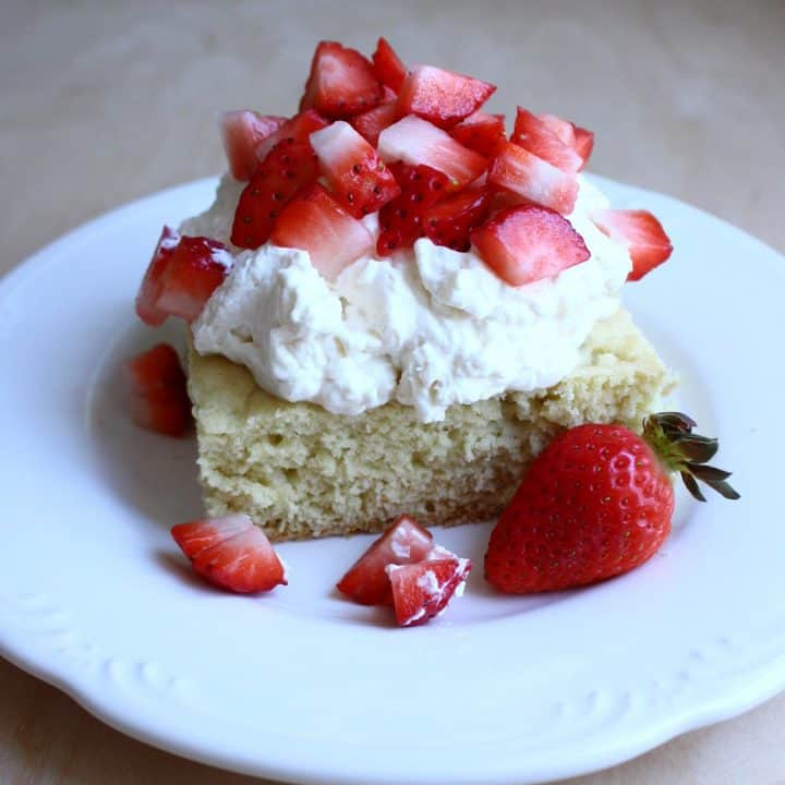 White plate with slice of sourdough shortcake with creamcheese whipped cream and cut up strawberries on top