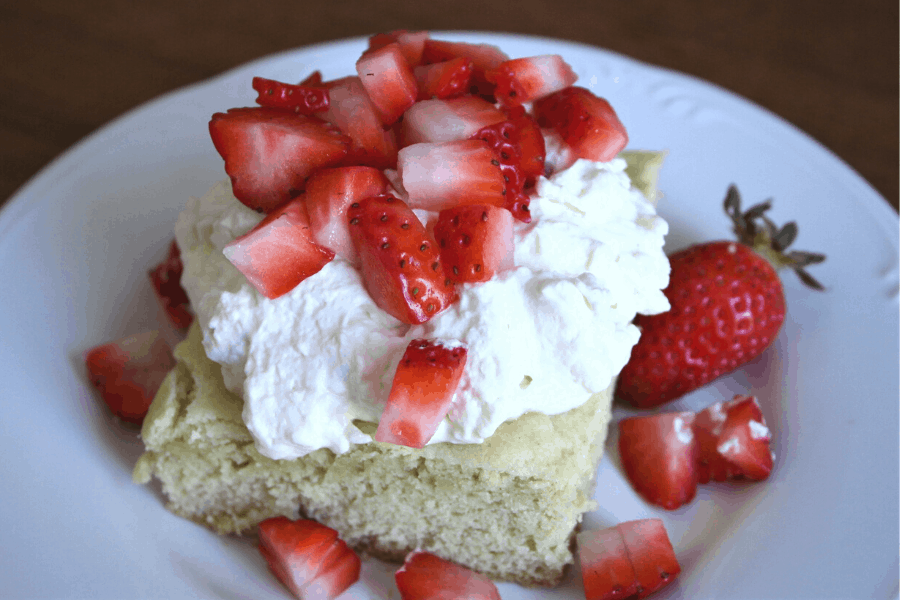 Plate with sourdough shortcake with whipped cream cheese frosting and strawberries on top