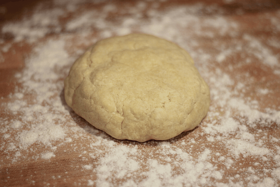 Ball of pie dough sitting on sprinkled flour on kitchen counter