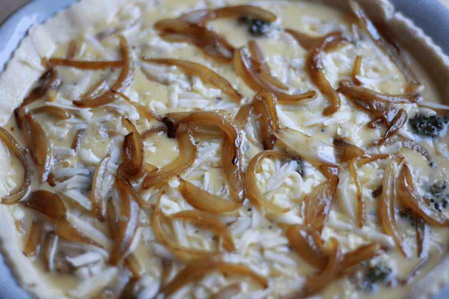 caramelized onion broccoli quiche ready to be baked