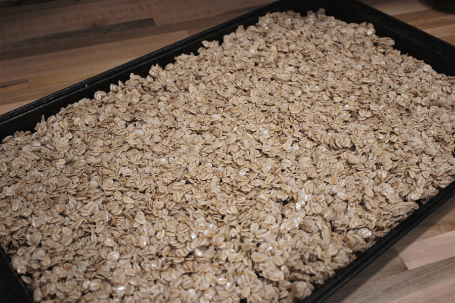 easy granola recipe evenly spread out on cookie sheet ready to be baked