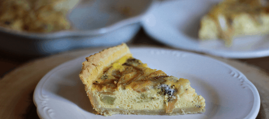 piece of quiche on white plate and pie dish in backround