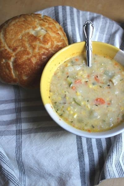 small loaf of bread sitting on a grey and white dish towel next to a bowl of zucchini corn chowder
