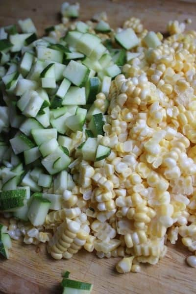 chopped up zucchini and fresh corn cut off the cob on a wooden cutting board