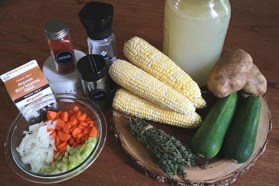 ingredients for zucchini corn chowder sitting on a wooden cutting board and wooden table