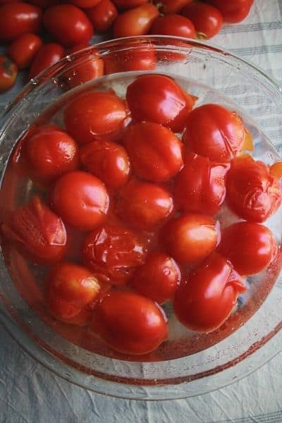 blanched tomatoes in a large glass bowl of ice water