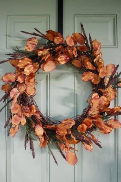 DIY fall wreath hanging on a light green front door